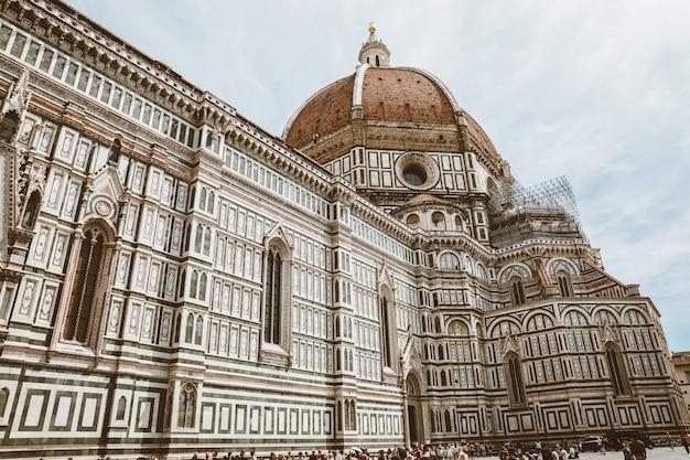 Florence, italië - 24 juni, 2018: panoramisch uitzicht op de cattedrale di santa maria del fiore (kathedraal van de heilige maria van de bloem) en giotto's campanile. mensen lopen op het plein in de zomerdag