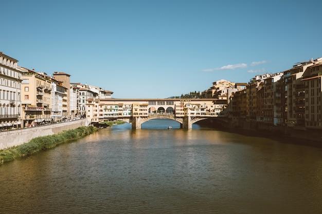 Florence, italië - 26 juni, 2018: panoramisch uitzicht op de ponte vecchio (oude brug) is een middeleeuwse stenen boogbrug met gesloten spandrel over de rivier de arno, in florence. zomerdag en blauwe lucht