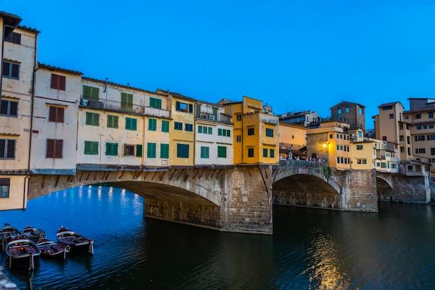 Florence, italië - circa juni 2021: zonsondergang op de ponte vecchio - oude brug. verbazingwekkend blauw licht voor de avond.