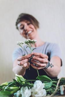 Flower trends 2021, natuurlijkheid, bloemschikken, bloemistentrucs, tips. kleine onderneming. floral design studio, het maken van decoraties en arrangementen. bloemist vrouw maakt fruit eetbaar boeket.
