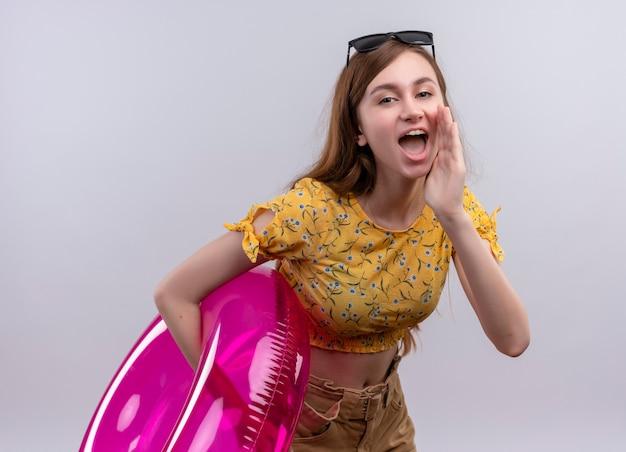 Fluisterende jong meisje draagt ?? een zonnebril op het hoofd met zwemmen ring hand zetten in de buurt van de mond op geïsoleerde witte muur