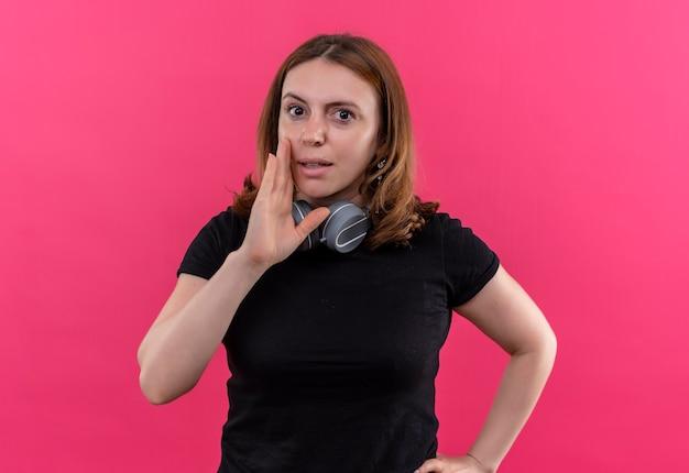 Fluisterende jonge casual vrouw met koptelefoon op nek met hand neard mond op geïsoleerde roze muur