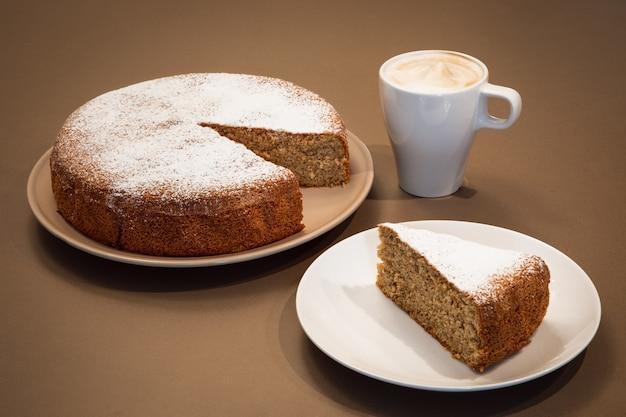 Fluitje van een cent gemaakt van amandelen en droog brood met cappuccino (antica torta alle mandorle e pane)