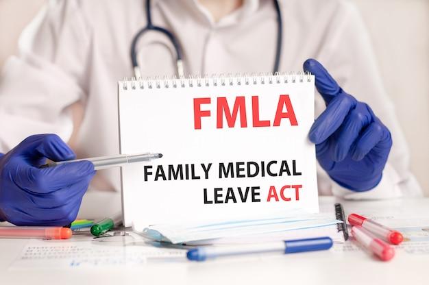Fmla-kaart in handen van arts. de arts dient blauwe handschoenen in met een vel papier met de tekst fmla - afkorting van family medical leave act, medisch concept.