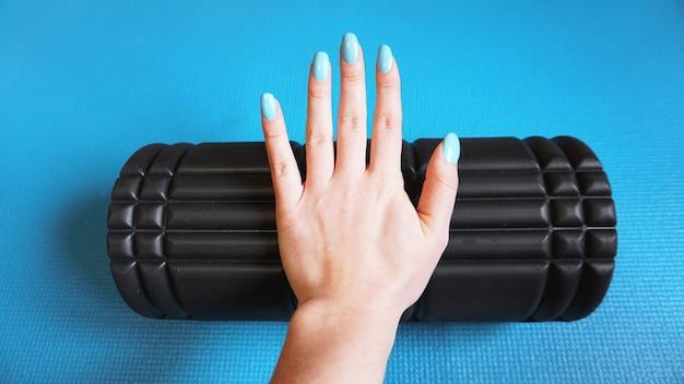 Foam roller gym fitnessapparatuur blauwe achtergrond zelf myofascial release - mfr. hand houdt een roller. hoe uitrusting voor sport te kiezen