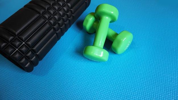Foam roller met groene dumbbells gym fitnessapparatuur blauwe achtergrond zelf myofascial release - mfr.