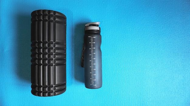 Foam roller met waterfles gym fitnessapparatuur blauwe achtergrond zelf myofascial release - mfr.