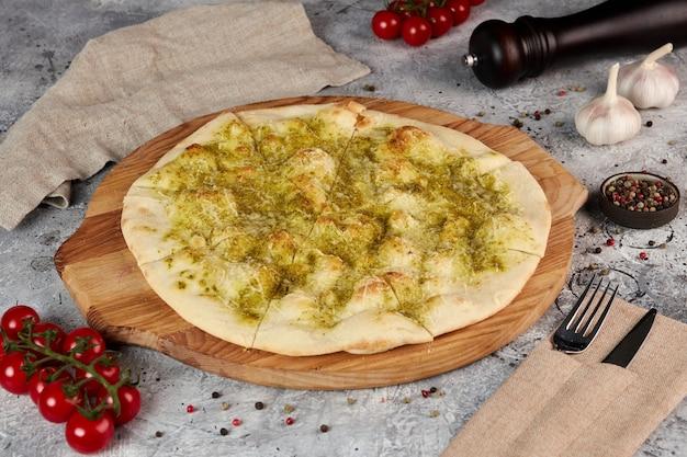 Focaccia met pesto en parmezaanse kaas op houten bord, grijze achtergrond
