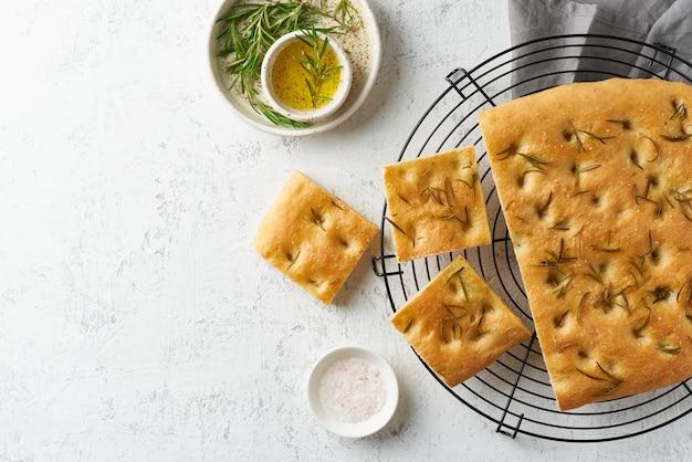 Focaccia, pizza, italiaans plat brood met rozemarijn en olijfolie op rooster