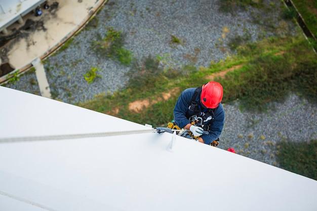 Focus bovenaanzicht mannelijke werknemer naar beneden hoogte tank dak touw toegang veiligheidsinspectie van dikte opslagtank gas propaan.