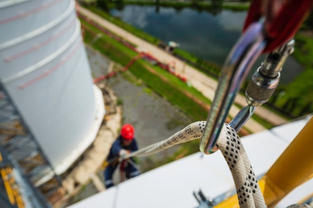 Focus bovenaanzicht mannelijke werknemer naar beneden karabijnhaak touw hoogte tank dak knoop leuning touw toegang veiligheidsinspectie van dikte opslagtank dak.
