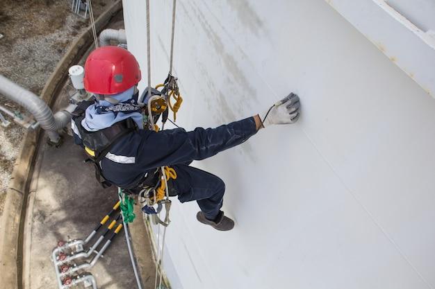Focus bovenaanzicht mannelijke werknemer touwtoegangsinspectie van de industrie van dikteopslagtanks
