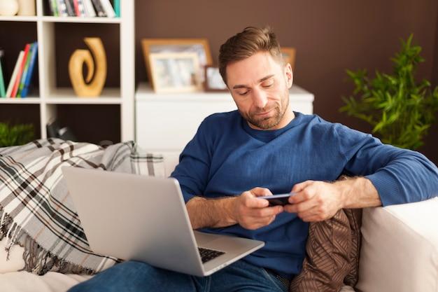 Focus man met behulp van mobiele telefoon en laptop thuis