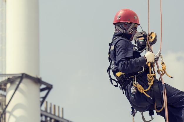 Focus mannelijke werknemer met behulp van touwtoegang van inspectieopslagtank