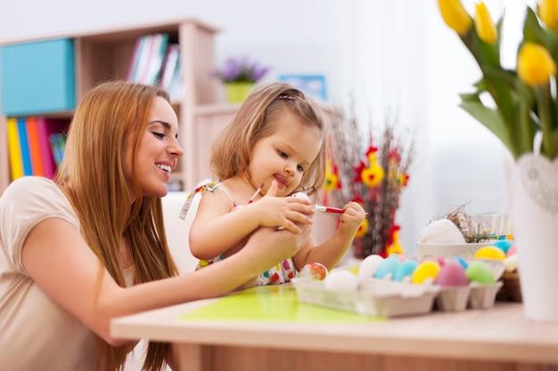 Focus meisje schilderij paaseieren met moeder