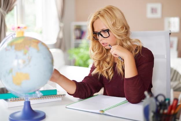 Focus meisje studeren globe van aarde thuis