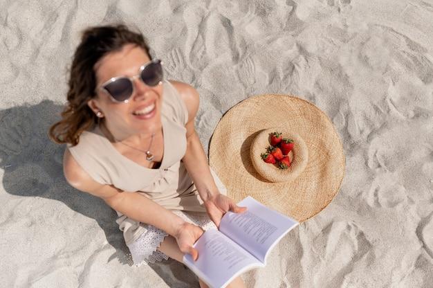 Focus op aardbeien op een strohoed op het zand op het strand. en wazig gelukkig lachende jonge vrouw zittend op het zand een boek lezen en lachend opzoeken. van bovenaf geschoten.