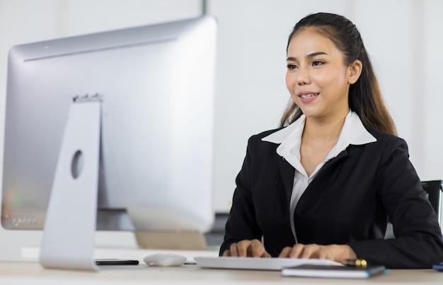 Focus op aziatische vrouwelijke kantoormensen die een pak dragen dat aan een bureau zit en een computer gebruikt terwijl ze glimlachen