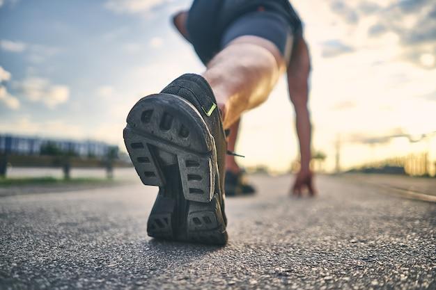 Focus op de buitenzool van de zwarte hardloopschoen voor heren bij de start voor de race