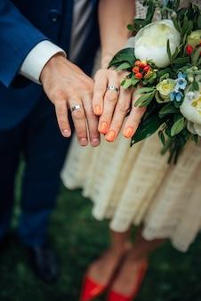 Focus op de handen van bruid en bruidegom, bruidsboeket