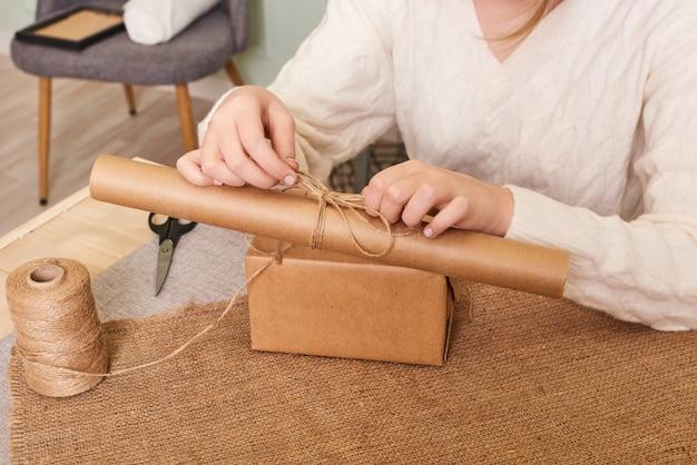 Focus op de handen van de vrouw in witte gebreide trui verpakking. ambachtelijk inpakpapier en natuurlijk touw. fijne vakantie aanwezig, verrassing. cadeaus voor tweede kerstdag
