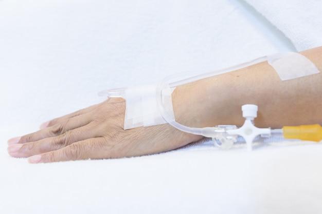 Focus op de handen van vrouwelijke patiënten nemen zoutoplossing intraveneus in het ziekenhuis.