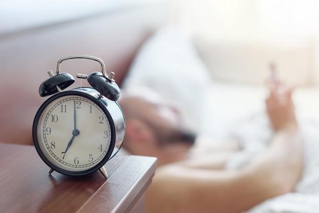 Focus op de wekker, man wordt vroeg in de ochtend wakker, gezond slaapconcept, luidruchtig effect voor de atmosfeer