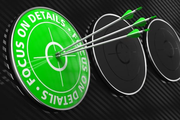 Focus op details-slogan. drie pijlen raken het midden van groene doel op zwarte achtergrond.