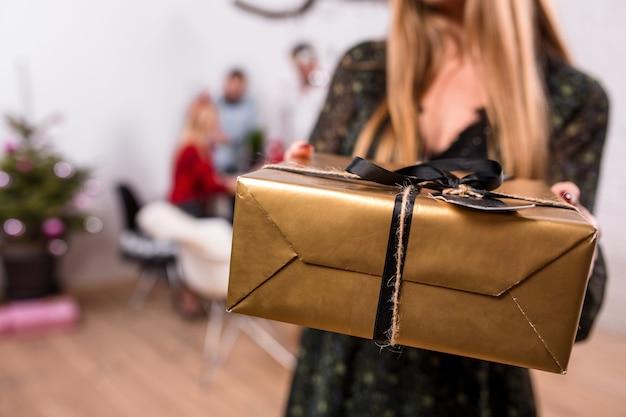 Focus op een geschenkdoos in handen van de vrouw op de voorgrond mooie blonde in een kerstmuts en zwarte jurk