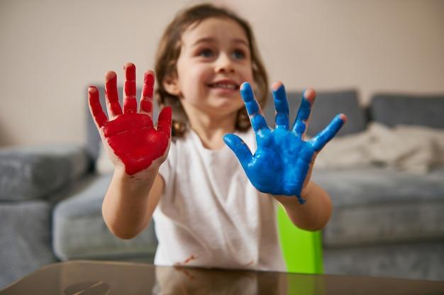 Focus op geschilderde handen in blauwe en rode verf van een schattig klein meisje