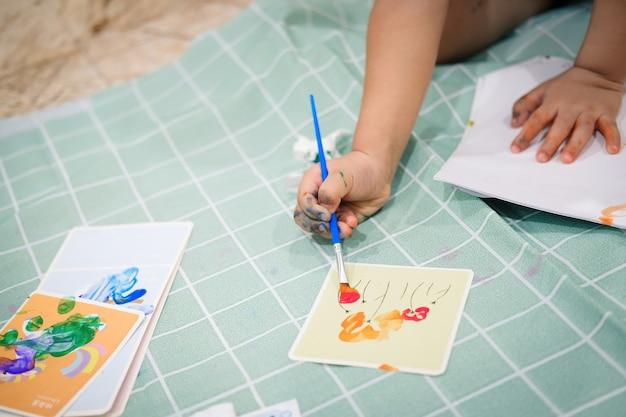 Focus op handen op papier. kinderen gebruiken penselen om waterverf op papier te schilderen om hun verbeeldingskracht te creëren en hun leervaardigheden te verbeteren.