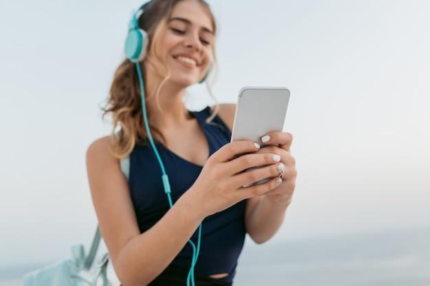 Focus op handen van gelukkige jonge vrouw in sportkleding chatten op telefoon, luisteren naar muziek via koptelefoon op zee. glimlachen, echte positieve emoties uitdrukken