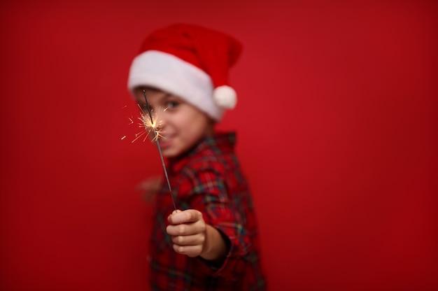Focus op het vuur schittert in de sparkler bengalen lichten in de hand van wazig kind in kerstman hoed en geruit hemd, geïsoleerd over rood gekleurde achtergrond met kopie ruimte voor kerstadvertentie