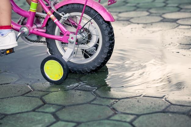 Focus op het wiel in water, kind meisje paardrijden fiets in park