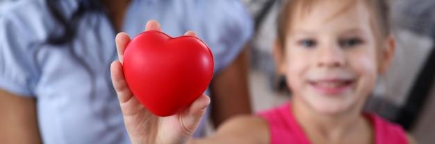Focus op kind hand met speelgoed rood hart. liefdevolle relatie tussen moeder en dochter. gelukkig meisje dat camera met geluk bekijkt. familie en moederschap concept