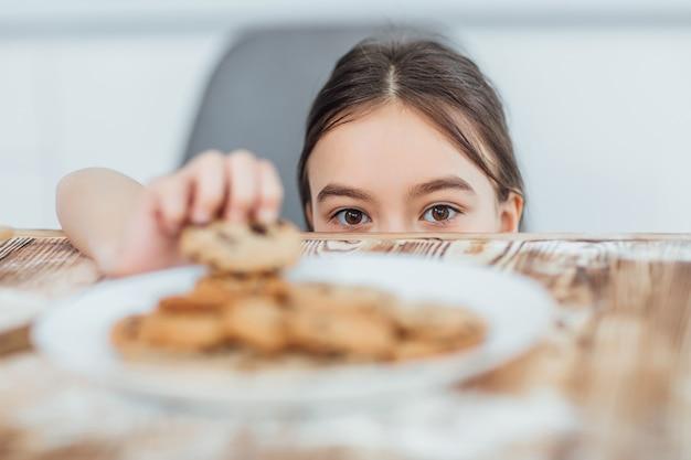 Focus op klein meisje steelt koekje