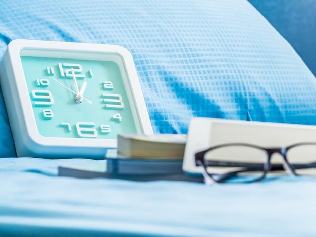 Focus op klok met wazig tablet, boeken en glazen in de slaapkamer.