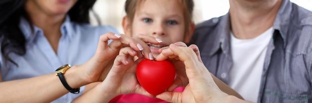 Focus op mensen handen met rood hart in handen bij elkaar. klein kind zitten met moeder, vader en camera kijken met geluk.