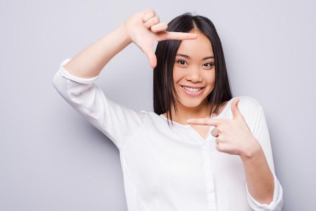 Focus op mij. mooie jonge aziatische vrouw die naar de camera kijkt en een vingerframe gebaart terwijl ze tegen een grijze achtergrond staat