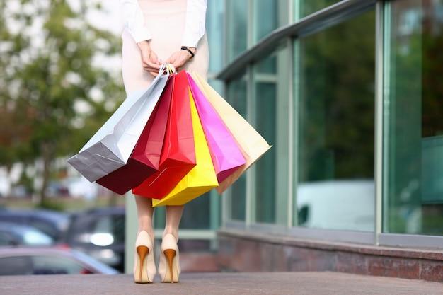 Focus op mooi model in lichte kleding die zich in de buurt van modieuze boetiek bevindt en veelkleurige winkelpakketten houdt. mode en winkelen concept.