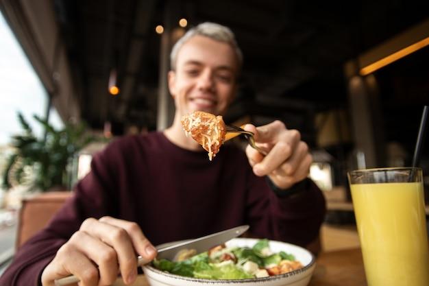 Focus op plakje kip met kaas. gezond voedselconcept. wazig blonde man caesar salade eten en sinaasappelsap drinken