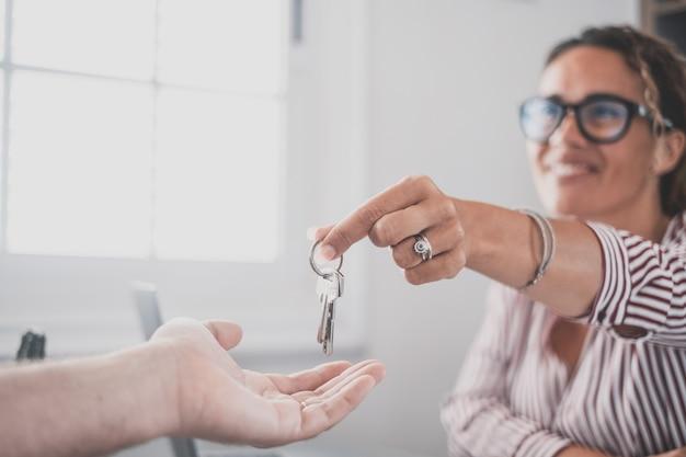 Focus op sleutelbos van huis flat appartement in de hand van lachende vrouw wazig portret