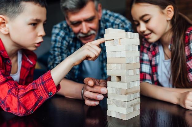 Focus op twee gelukkige broers en zussen die een spel spelen met grootvader die thuis vreugdevol houten blokken speelt.