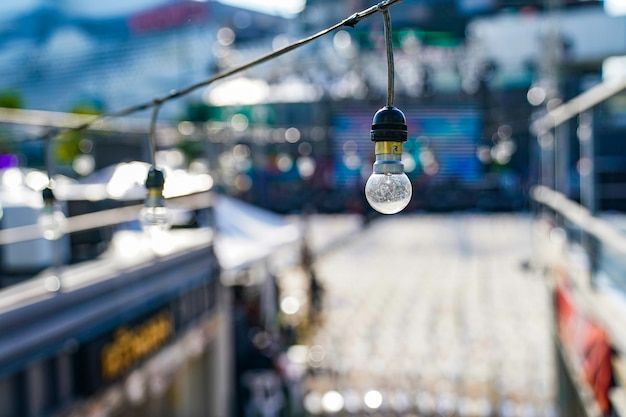 Focus op vintage cirkel hangende lamp op de lijn met onscherpte openluchtconcert op een dag achtergrond.