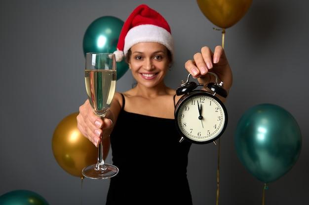 Focus op wekker met middernacht op de wijzerplaat en mousserende wijn glas in de handen van vrolijke vrouw met kerstmuts en lachende feestelijke grijze achtergrond met glanzende luchtballen voor kerstadvertentie