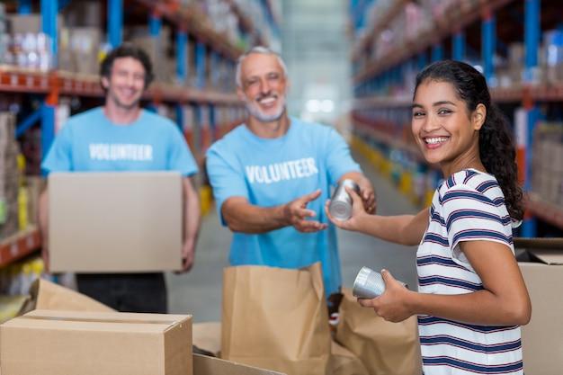 Focus van gelukkige vrouw geeft sommige goederen aan vrijwilligers