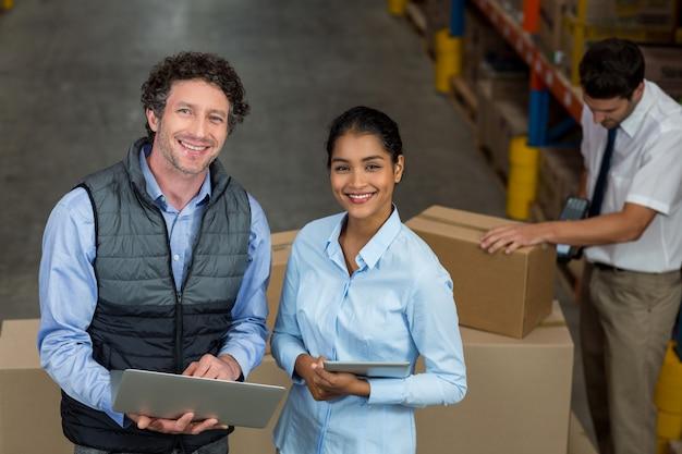 Focus van twee managers glimlachen en poseren tijdens het werk