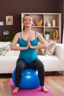 Focus vrouw tijdens pilates tijdens de zwangerschap thuis
