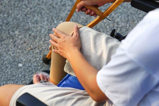 Focusbeeld van de hand van de patiënt die een kruk vasthoudt terwijl hij op een rolstoel zit en een gewonde knie