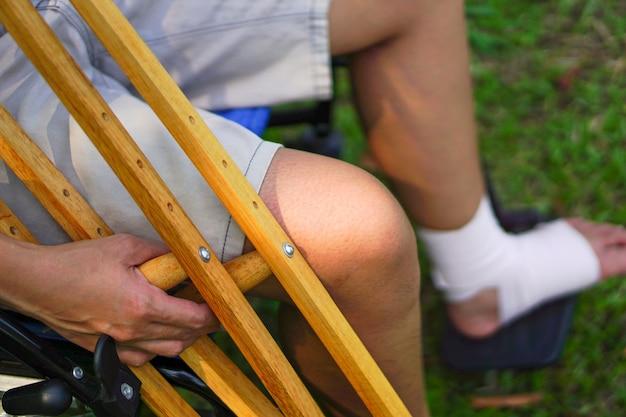 Focusbeeld van de hand van de patiënt die een kruk vasthoudt terwijl hij op een rolstoel zit en gewonde enkel